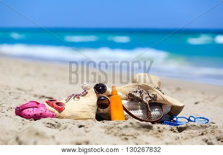 family vacation concept - beach bag, suncream, sandals on sand beach
