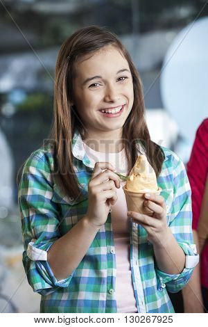 Happy Girl Holding Ice Cream In Cup At Parlor