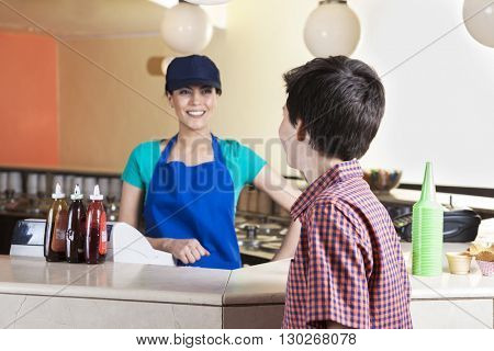 Waitress Looking At Customer At Counter In Ice Cream Parlor