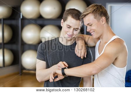 Male Friends Checking Pedometer In Gym