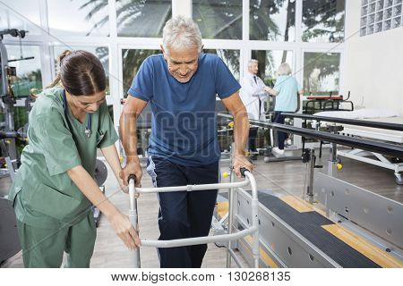 Nurse Assisting Senior Man To Walk Using Walker