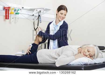 Physiotherapist Helping Senior Woman With Leg Exercise