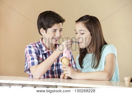 Boy Feeding Strawberry Ice Cream To Sister At Counter