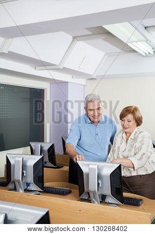 Happy Senior People Using Computer In Classroom