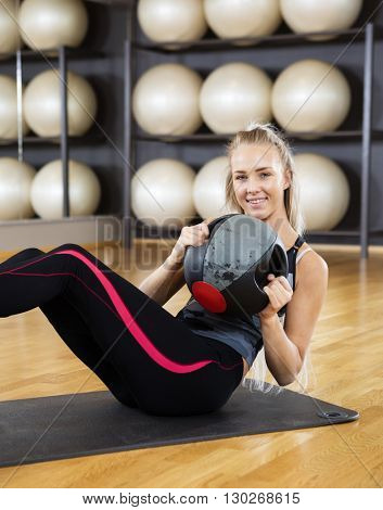 Confident Woman Exercising With Medicine Ball In Gym