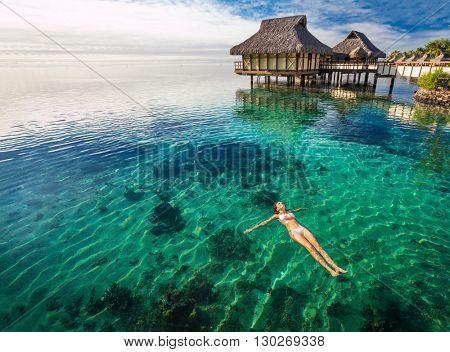 Woman in white bikini swimming in coral lagoon at the resort, Moorea, Tahiti