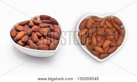 Almonds in a heart shaped bowl, isolated on white