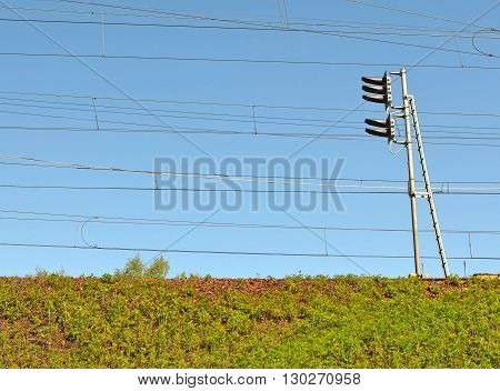 Bottom view on railway embankment covered with gravel and overgrown grass. Higher traffic light and numerous electric wires against blue sky. Image can be used as background.