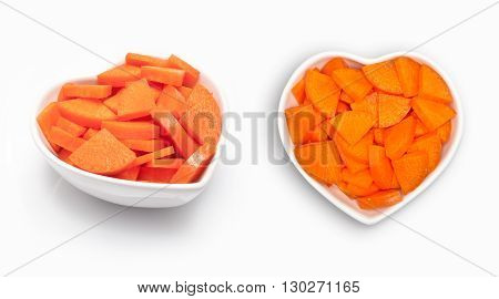 carrot slices  in a heart shaped bowl, isolated on white