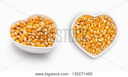 Corn seeds   in a heart shaped bowl, isolated on white