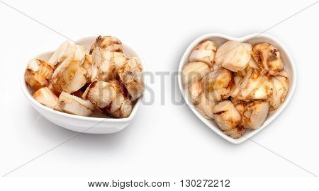 Fresh galangal  in a heart shaped bowl, isolated on white