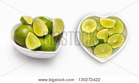 sliced lime  in a heart shaped bowl, isolated on white
