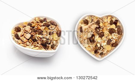 Muesli  in a heart shaped bowl, isolated on white