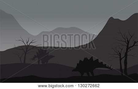 Gray silhouette of two stegosaurus in the hills
