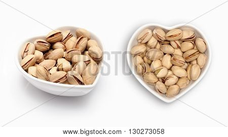 Pistachio in a heart shaped bowl, isolated on white