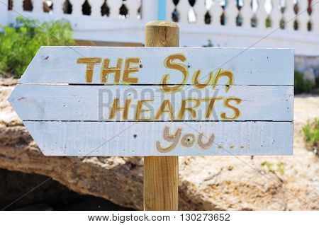 closeup of a white wooden signpost attached to a wooden pole with the text the sun hearts you written in it, pointing the direction towards the beach