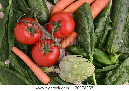 high-angle shot of a pile of different raw vegetables, such as spinach, artichokes, cucumbers, zucchinis, green peppers, tomatoes and carrots