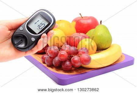 Hand of woman with glucometer and fresh natural fruits on cutting board concept for healthy eating and diabetes
