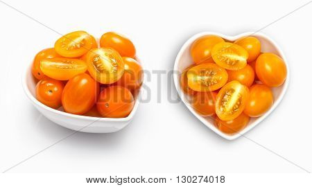 Plum tomato  in a heart shaped bowl, isolated on white