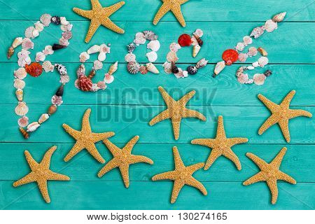 Colorful creative Beach still life sign with the word Beach formed of assorted seashells above scattered starfish on a colorful green stained wood background