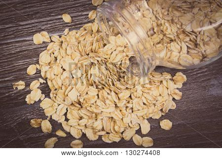 Vintage photo Heap of organic oatmeal oat flakes spilling out of glass jar on wooden background concept for healthy eating and nutrition