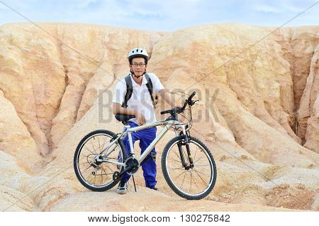 Asian man with mountain bike on rocks. Sport and active life concept.