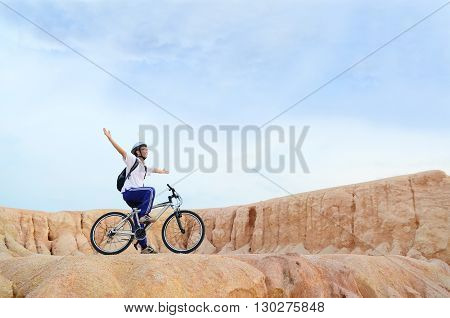 Cyclist on the top of a hill with their hands up