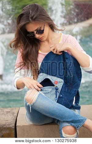 young woman in casual clothes and jeans with sunglasses take a break by fountain summer day at city