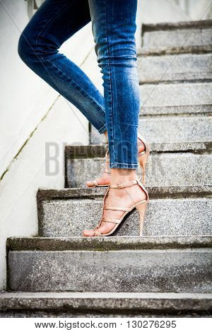 woman legs in blue jeans and high heel golden sandals on stairs day shot in the city