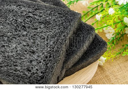 charcoal bread black bread in wooden dish on sack background.