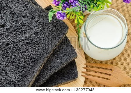 loaf of charcoal bread black bread and milk glass.