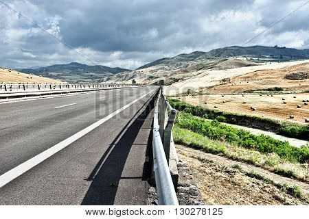 Landscape of Sicily with Highway and Many Hay Bales