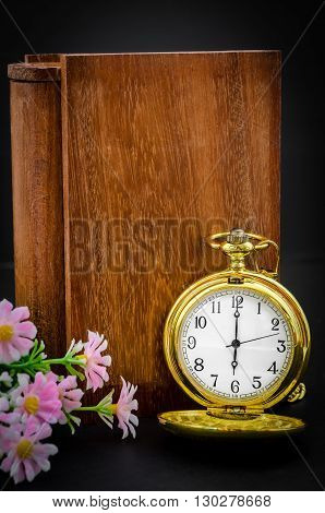 Wood book cover with golden pocket watch on black background.