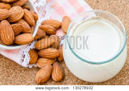 Almond milk in glass with almonds seeds on wood table.