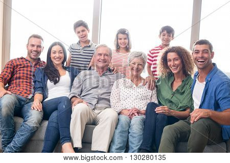 Portrait of happy family sitting on sofa in their living room