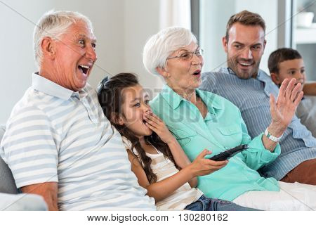 Happy family sitting on sofa watching television in their living room