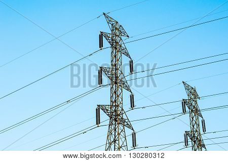 The High voltage transmission lines isolated on blue sky background