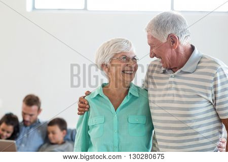 Senior couple embracing each other and smiling in living room