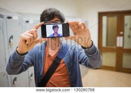 Student taking his selfie on smartphone in locker room