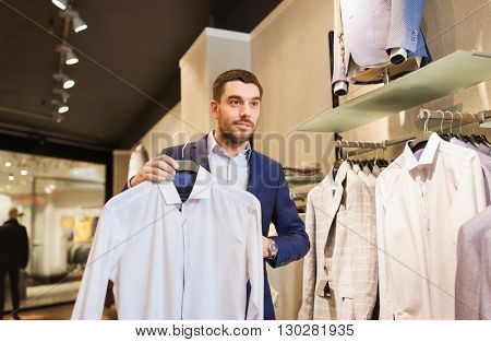 sale, shopping, fashion, style and people concept - elegant young man in suit choosing shirt in mall or clothing store