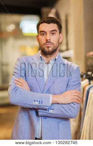 sale, shopping, fashion, style and people concept - young handsome man in jacket at clothing store