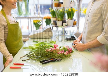 people, shopping, sale, floristry and consumerism concept - close up of happy florist woman making bouquet for and man or customer at flower shop