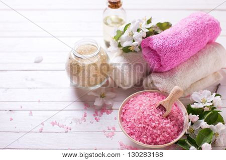 Spa or wellness setting. Sea salt in bowl towels aroma oil in bottle and flowers on white wooden background. Selective focus. Place for text.