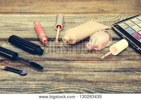 Cosmetics: mascara, concealer, nail polish, perfume, lip gloss and eye shadow on wooden background. Toned image.