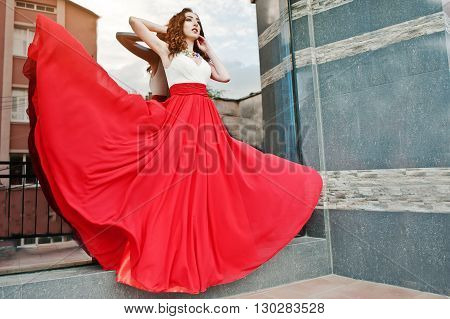 Portrait Of Fashionable Girl At Red Evening Dress Posed Background Mirror Window Of Modern Building.