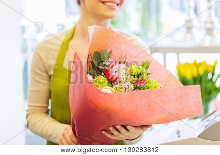people, business, sale and floristry concept - close up of happy smiling florist woman holding bunch of flowers wrapped into paper at flower shop