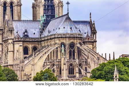 Flying Butresses Spires Towers Overcast Skies Notre Dame Cathedral Paris France. Notre Dame was built between 1163 and 1250 AD. Black Spire erected in the 1850s.