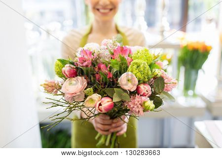 people, business, sale and floristry concept - close up of florist woman holding bunch at flower sho