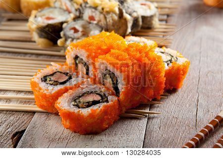 Maki Sushi - Roll with Cream Cheese, Salmon and Avocado inside. Tobiko (flying fish roe) outside.