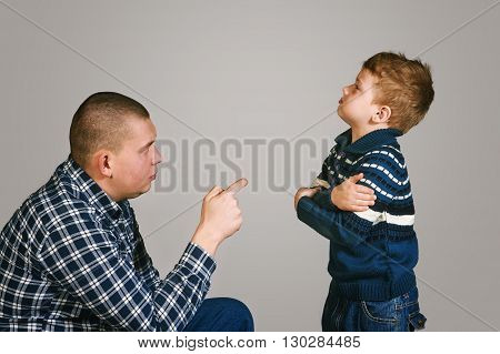 father teaches his son on grey background